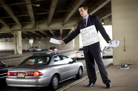 Recent La Salle graduate hands resumes out to passing cars during rush hour in Philadelphia